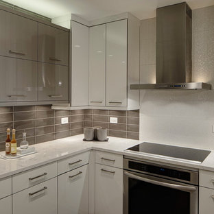 Enclosed kitchen - small contemporary u-shaped porcelain floor enclosed kitchen idea in Chicago with flat-panel cabinets, white cabinets, solid surface countertops, gray backsplash, glass tile backsplash, stainless steel appliances and no island