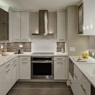 Design ideas for a small contemporary u-shaped kitchen in Chicago with an undermount sink, flat-panel cabinets, white cabinets, solid surface benchtops, grey splashback, glass tile splashback, stainless steel appliances, porcelain floors and no island.