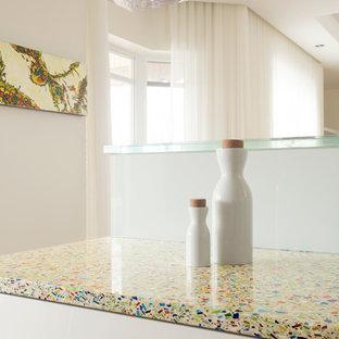 Exemple d'une cuisine parallèle moderne fermée et de taille moyenne avec un évier encastré, un placard à porte plane, des portes de placard blanches, un plan de travail en verre recyclé, une crédence blanche, une crédence en feuille de verre, un électroménager blanc, un sol en bois clair et aucun îlot.