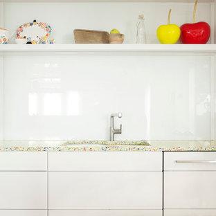 Ejemplo de cocina de galera, actual, de tamaño medio, cerrada, sin isla, con fregadero bajoencimera, armarios con paneles lisos, puertas de armario blancas, encimera de vidrio reciclado, salpicadero blanco, salpicadero de vidrio templado, electrodomésticos blancos y suelo de madera clara