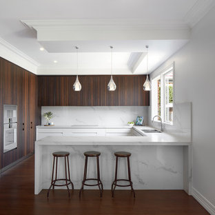 Photo of a large contemporary u-shaped kitchen in Melbourne with a double-bowl sink, flat-panel cabinets, dark wood cabinets, white splashback, stainless steel appliances, white benchtop, marble benchtops, marble splashback, light hardwood floors and with island.