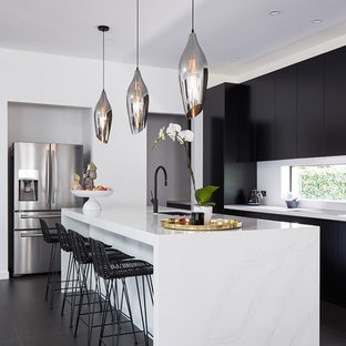 Design ideas for a contemporary l-shaped kitchen in Sydney with an undermount sink, flat-panel cabinets, black cabinets, window splashback, stainless steel appliances, with island, black floor and white benchtop.