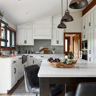 На фото: п-образная кухня среднего размера в стиле рустика с обеденным столом, раковиной в стиле кантри, белыми фасадами, стеклянной столешницей, серым фартуком, фартуком из стеклянной плитки, техникой под мебельный фасад, паркетным полом среднего тона, островом, коричневым полом, белой столешницей и фасадами с декоративным кантом