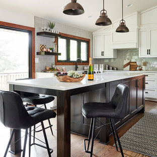 Mid-sized rustic eat-in kitchen ideas - Eat-in kitchen - mid-sized rustic u-shaped medium tone wood floor and brown floor eat-in kitchen idea in Other with a farmhouse sink, recessed-panel cabinets, white cabinets, glass countertops, gray backsplash, glass tile backsplash, paneled appliances, an island and white countertops