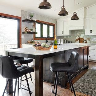 Mittelgroße Rustikale Wohnküche in U-Form mit Landhausspüle, Schrankfronten mit vertiefter Füllung, weißen Schränken, Glas-Arbeitsplatte, Küchenrückwand in Grau, Rückwand aus Glasfliesen, Elektrogeräten mit Frontblende, braunem Holzboden, Kücheninsel, braunem Boden und weißer Arbeitsplatte in Sonstige