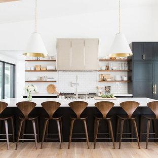 Imagen de cocina clásica renovada con salpicadero blanco, salpicadero de azulejos tipo metro, suelo de madera clara, una isla, armarios abiertos y electrodomésticos con paneles