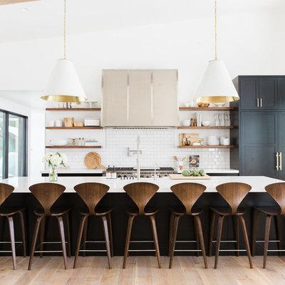 Kitchen - transitional light wood floor kitchen idea in Salt Lake City with white backsplash, subway tile backsplash, an island, open cabinets and paneled appliances
