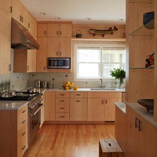 Diseño de cocina comedor en L, moderna, grande, con fregadero de un seno, armarios con paneles lisos, puertas de armario de madera clara, encimera de vidrio, salpicadero verde, salpicadero de azulejos de vidrio, electrodomésticos de acero inoxidable, suelo de madera clara, una isla y suelo marrón