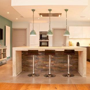 サリーの広いモダンスタイルのおしゃれなキッチン (ドロップインシンク、フラットパネル扉のキャビネット、グレーのキャビネット、コンクリートカウンター、青いキッチンパネル、パネルと同色の調理設備、磁器タイルの床、グレーの床、グレーのキッチンカウンター) の写真