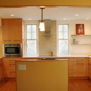 バーリントンの中サイズのモダンスタイルのおしゃれなアイランドキッチン (フラットパネル扉のキャビネット、中間色木目調キャビネット、無垢フローリング、アンダーカウンターシンク、人工大理石カウンター、シルバーの調理設備) の写真