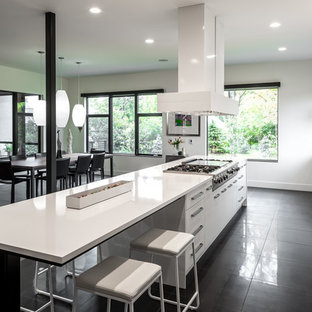 Photo of an expansive contemporary galley open plan kitchen in Minneapolis with with island, a single-bowl sink, flat-panel cabinets, white cabinets, quartz benchtops, white splashback, white appliances and porcelain floors.