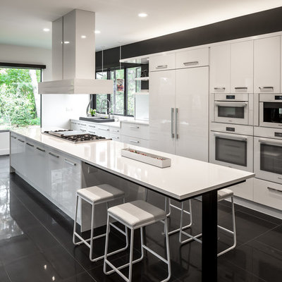 Open concept kitchen - huge contemporary galley porcelain tile and black floor open concept kitchen idea in Minneapolis with flat-panel cabinets, white cabinets, white appliances, an island, a single-bowl sink, quartz countertops, white backsplash and white countertops
