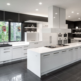 Expansive contemporary galley open plan kitchen in Minneapolis with flat-panel cabinets, white cabinets, with island, a single-bowl sink, quartz benchtops, white splashback, white appliances and porcelain floors.