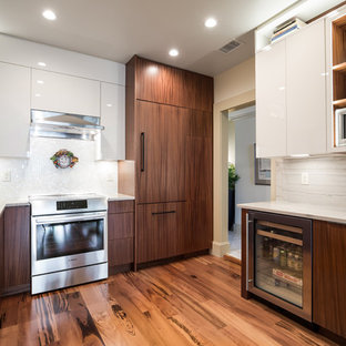 This is an example of a mid-sized scandinavian u-shaped eat-in kitchen in Jacksonville with an undermount sink, flat-panel cabinets, white cabinets, quartzite benchtops, limestone splashback, stainless steel appliances, medium hardwood floors, no island, multi-coloured floor and white benchtop.