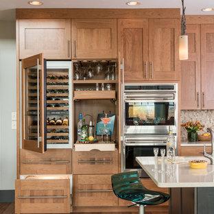 Modelo de cocina clásica renovada, de tamaño medio, con fregadero bajoencimera, armarios estilo shaker, puertas de armario de madera oscura, encimera de cuarzo compacto, salpicadero beige, salpicadero con mosaicos de azulejos, una isla y electrodomésticos de acero inoxidable