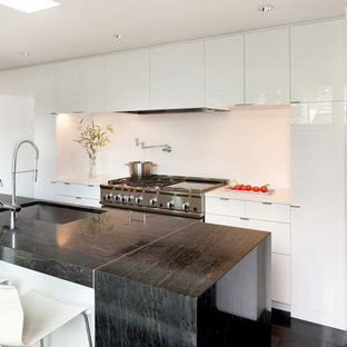 Mid-sized contemporary u-shaped separate kitchen in Seattle with an undermount sink, flat-panel cabinets, white cabinets, limestone benchtops, white splashback, stone slab splashback, panelled appliances, dark hardwood floors, with island, black floor and black benchtop.