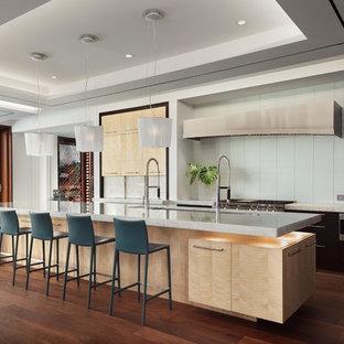 Foto de cocina comedor contemporánea con fregadero bajoencimera, armarios con paneles lisos, salpicadero blanco, salpicadero de azulejos de vidrio, electrodomésticos de acero inoxidable, suelo de madera oscura, una isla y suelo marrón