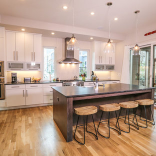 Contemporary kitchen designs - Kitchen - contemporary u-shaped light wood floor kitchen idea in Atlanta with a farmhouse sink, flat-panel cabinets, white cabinets, stainless steel appliances and an island
