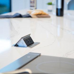 Offene, Mittelgroße Moderne Küche in L-Form mit Unterbauwaschbecken, flächenbündigen Schrankfronten, Quarzwerkstein-Arbeitsplatte, Küchenrückwand in Schwarz, weißen Elektrogeräten, Betonboden und Kücheninsel in Oklahoma City