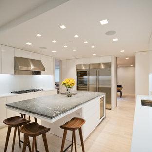 ニューヨークのモダンスタイルのおしゃれなキッチン (アンダーカウンターシンク、フラットパネル扉のキャビネット、白いキャビネット、大理石カウンター、白いキッチンパネル、石スラブのキッチンパネル、シルバーの調理設備、淡色無垢フローリング、緑のキッチンカウンター) の写真