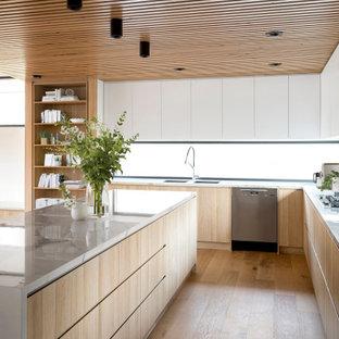 Ispirazione per una grande cucina design con lavello sottopiano, ante in legno chiaro, top in marmo, paraspruzzi a finestra, elettrodomestici in acciaio inossidabile, parquet chiaro, isola, pavimento marrone, top bianco e soffitto in perlinato