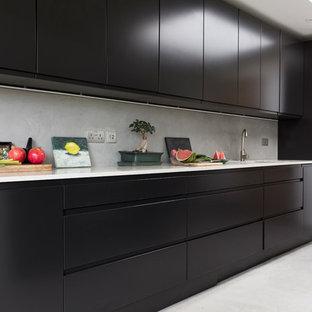 エディンバラの大きいエクレクティックスタイルのおしゃれなキッチン (一体型シンク、フラットパネル扉のキャビネット、黒いキャビネット、珪岩カウンター、グレーのキッチンパネル、パネルと同色の調理設備、コンクリートの床、グレーの床、白いキッチンカウンター、セメントタイルのキッチンパネル) の写真