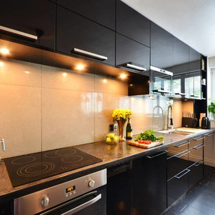 Photo of a small modern galley open plan kitchen in London with a drop-in sink, flat-panel cabinets, black cabinets, concrete benchtops, grey splashback, porcelain splashback, panelled appliances and bamboo floors.