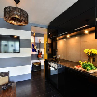 Design ideas for a small modern galley open plan kitchen in London with a drop-in sink, flat-panel cabinets, black cabinets, concrete benchtops, grey splashback, porcelain splashback, panelled appliances and bamboo floors.