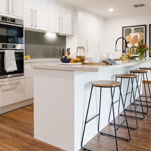 Large contemporary u-shaped kitchen in Melbourne with a double-bowl sink, open cabinets, white cabinets, quartz benchtops, metallic splashback, glass sheet splashback, stainless steel appliances, medium hardwood floors, with island and beige benchtop.