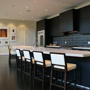 Immagine di un'ampia cucina ad ambiente unico minimal con lavello sottopiano, ante lisce, ante in legno bruno, top in cemento, paraspruzzi grigio, paraspruzzi in gres porcellanato, elettrodomestici in acciaio inossidabile, parquet scuro e penisola