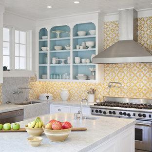 Ejemplo de cocina tradicional renovada con puertas de armario blancas, salpicadero amarillo, electrodomésticos de acero inoxidable y una isla