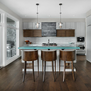 Contemporary kitchen remodeling - Example of a trendy l-shaped dark wood floor and brown floor kitchen design in Detroit with flat-panel cabinets, white cabinets, glass countertops, white backsplash, stainless steel appliances and an island