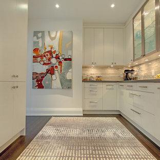 Modelo de cocina de galera, actual, con armarios con paneles lisos, electrodomésticos de acero inoxidable, suelo de madera oscura y salpicadero de piedra caliza