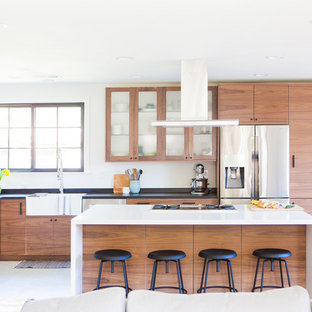 Small midcentury l-shaped open plan kitchen in San Francisco with a farmhouse sink, flat-panel cabinets, medium wood cabinets, multi-coloured splashback, ceramic splashback, stainless steel appliances, porcelain floors, with island, white floor and soapstone benchtops.