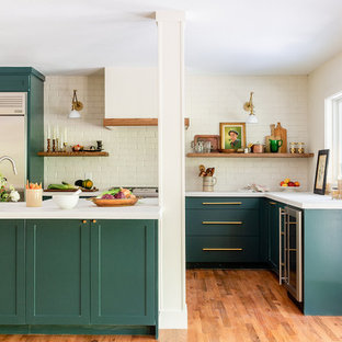 Inspiration for a mid-sized transitional l-shaped kitchen in Dallas with shaker cabinets, green cabinets, white splashback, brick splashback, stainless steel appliances, medium hardwood floors, with island, brown floor and white benchtop.