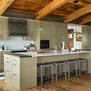 デンバーの巨大なラスティックスタイルのおしゃれなキッチン (シェーカースタイル扉のキャビネット、緑のキャビネット、白いキッチンパネル、パネルと同色の調理設備、淡色無垢フローリング、茶色い床、白いキッチンカウンター、板張り天井) の写真