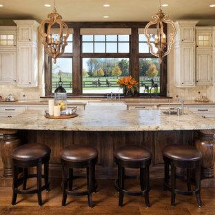Geräumige Urige Küche in U-Form mit Landhausspüle, profilierten Schrankfronten, Schränken im Used-Look, Granit-Arbeitsplatte, Küchenrückwand in Beige, Rückwand aus Steinfliesen, Küchengeräten aus Edelstahl, dunklem Holzboden, Kücheninsel und braunem Boden in Minneapolis