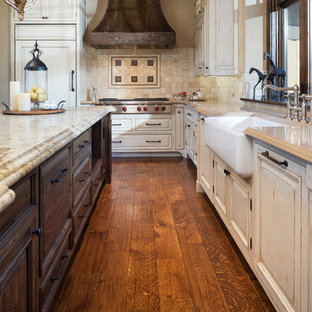 Inspiration for an expansive rustic u-shaped kitchen in Minneapolis with a belfast sink, raised-panel cabinets, distressed cabinets, granite worktops, beige splashback, stone tiled splashback, stainless steel appliances, an island, dark hardwood flooring and brown floors.