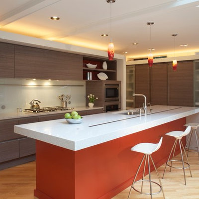 Kitchen - modern l-shaped kitchen idea in DC Metro with an undermount sink, flat-panel cabinets, glass sheet backsplash and paneled appliances