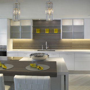 This is an example of a mid-sized modern single-wall open plan kitchen in Miami with an undermount sink, flat-panel cabinets, white cabinets, solid surface benchtops, brown splashback, timber splashback, stainless steel appliances, porcelain floors, a peninsula, beige floor and white benchtop.