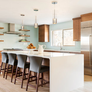 Contemporary kitchen pictures - Kitchen - contemporary l-shaped light wood floor and beige floor kitchen idea in Salt Lake City with flat-panel cabinets, medium tone wood cabinets, blue backsplash, glass sheet backsplash, stainless steel appliances, an island and white countertops