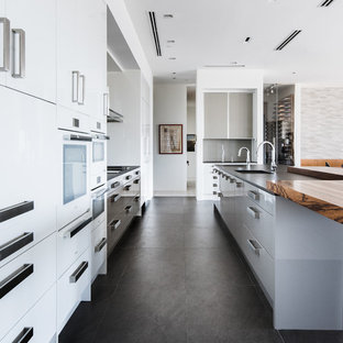 Large contemporary eat-in kitchen designs - Large trendy single-wall porcelain floor and gray floor eat-in kitchen photo in Dallas with an undermount sink, flat-panel cabinets, white cabinets, quartz countertops, gray backsplash, porcelain backsplash, white appliances and an island