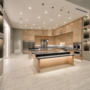 This is an example of a large contemporary l-shaped open plan kitchen in Houston with an integrated sink, flat-panel cabinets, medium wood cabinets, quartz benchtops, multi-coloured splashback, glass tile splashback, stainless steel appliances, porcelain floors and multiple islands.