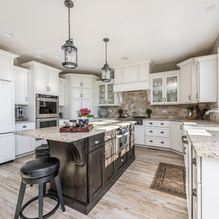 Large traditional u-shaped open plan kitchen in Chicago with a farmhouse sink, recessed-panel cabinets, white cabinets, brown splashback, panelled appliances, light hardwood floors, with island, beige floor, beige benchtop, granite benchtops and stone tile splashback.