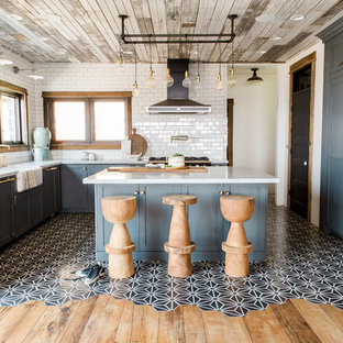 Inspiration for an urban u-shaped kitchen in Salt Lake City with shaker cabinets, blue cabinets, white splashback, metro tiled splashback, integrated appliances, cement flooring, an island, multi-coloured floors and white worktops.