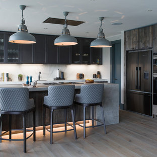 Medium sized classic l-shaped kitchen/diner in Berkshire with a built-in sink, shaker cabinets, grey cabinets, laminate countertops, white splashback, marble splashback, integrated appliances, an island and grey worktops.