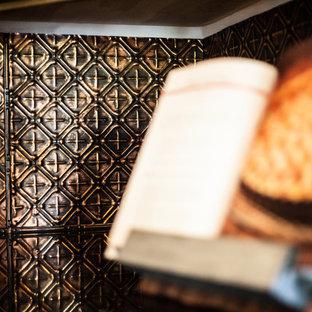 Idee per una grande cucina rustica con lavello a tripla vasca, ante con bugna sagomata, top in granito, paraspruzzi a effetto metallico, paraspruzzi con piastrelle di metallo, elettrodomestici da incasso, pavimento in mattoni e isola