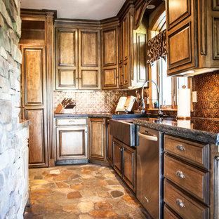 Idee per una grande cucina stile rurale con lavello a tripla vasca, ante con bugna sagomata, top in granito, paraspruzzi a effetto metallico, paraspruzzi con piastrelle di metallo, elettrodomestici da incasso, pavimento in mattoni e isola