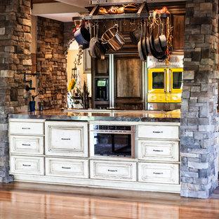 Immagine di una grande cucina rustica con lavello a tripla vasca, ante con bugna sagomata, top in granito, paraspruzzi a effetto metallico, paraspruzzi con piastrelle di metallo, elettrodomestici da incasso, pavimento in mattoni e isola