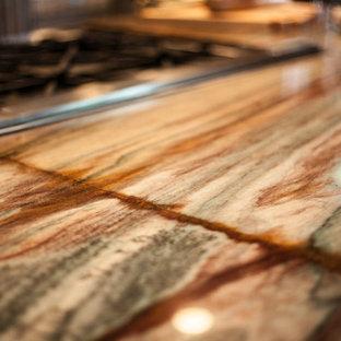 Ispirazione per una grande cucina stile rurale con lavello a tripla vasca, ante con bugna sagomata, top in granito, paraspruzzi a effetto metallico, paraspruzzi con piastrelle di metallo, elettrodomestici da incasso, pavimento in mattoni e isola
